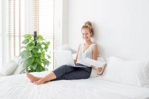 Lucht zuiverende plant op slaapkamer en vrouw op bed